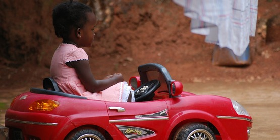 A girl playing with her toy car