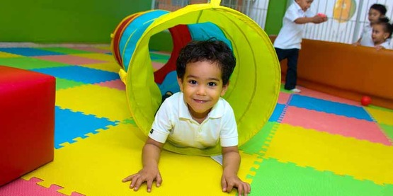 young boy in a playroom crawling in a play tube