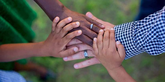 hands of parents and children in interracial family