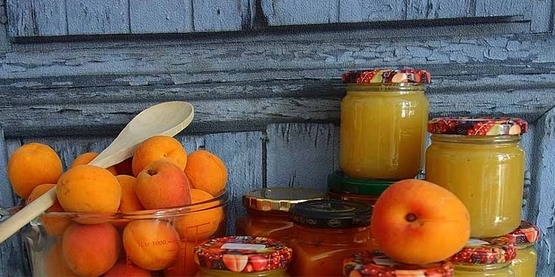 fresh apricots in a bowl, next to several jars of preserves