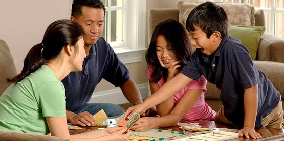 An Asian family (adult male and female and two adolescents, male and female) sitting around a coffee table playing a board game.