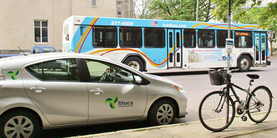 Ithaca Carshare car, TCAT bus, and parked bicycle in downtown Ithaca.