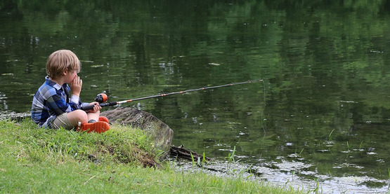 child sitting on bank by water with fishing pole