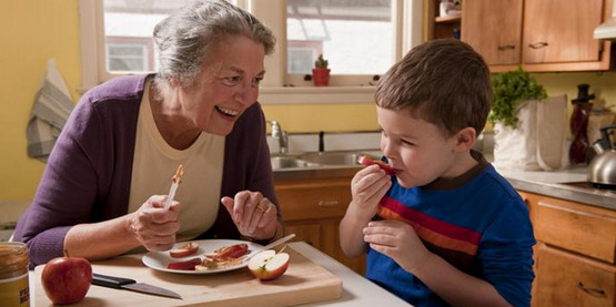 An older woman and a young boy prepare a healthy snack.