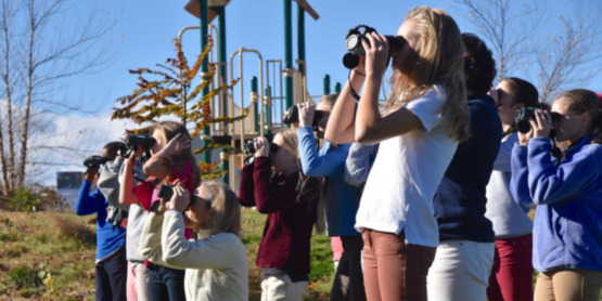 children with binoculars watching something ins the distance