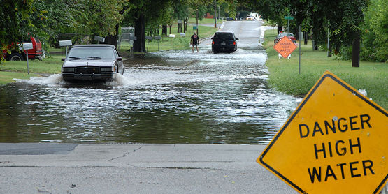 Oklahoma, Okla., August 19, 2007 -- Cars drive though a flooded street carefully after heading the High Water Danger Signs. FEMA has a preparedness program to make people aware of the dangers of driving though flooded roads.