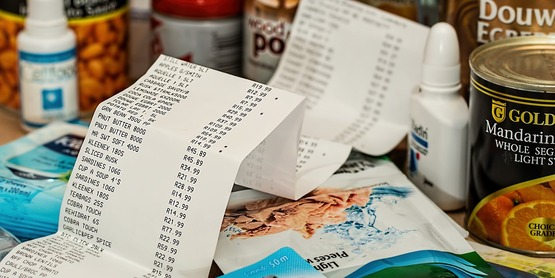 A long grocery receipt surrounded by food