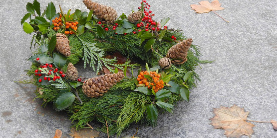 photograph of an evergreen wreath decorated with pinecones and berries