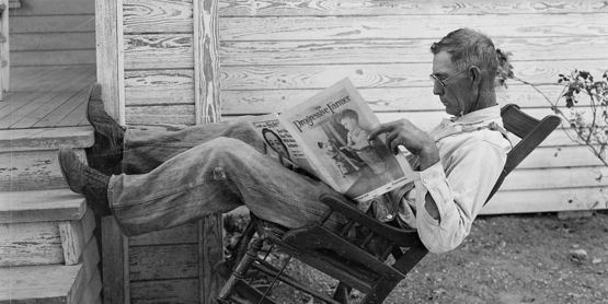 "Farmer in rocking-chair reading The Progressive Farmer. ""Farmer reading his farm paper"" By George W. Ackerman, Coryell County, Texas, September 1931"