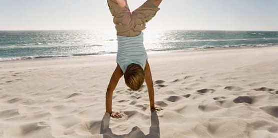 boy performing a handstand at the beach