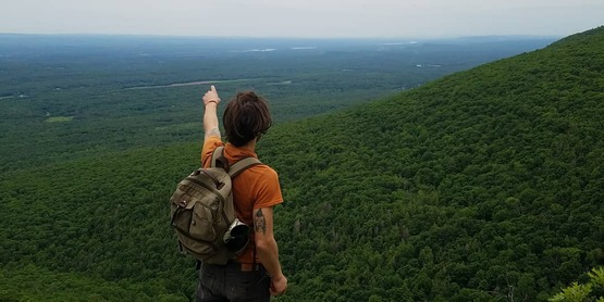 man pointing over a scenic lookout
