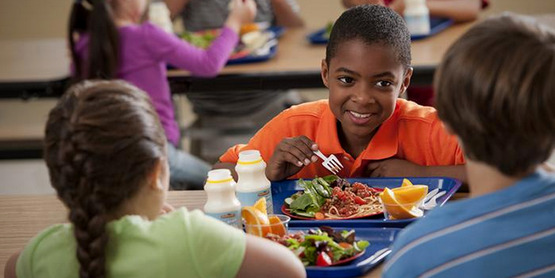 A group of children have lunch in the school cafeteria.