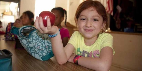 Young girl in a school cafeteria holding an apple