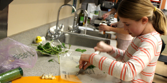 young girl using chef's knife during Kids in the Kitchen Cooking series