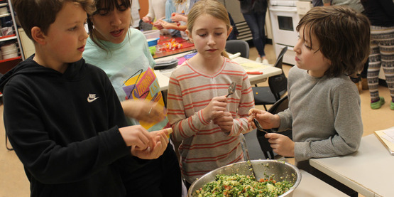 Youth seasoning tabouli during Fall 2019 Kids in the Kitchen Cooking series