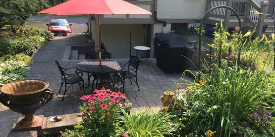The hillside overlooks a paver patio.