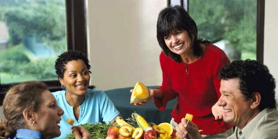 A nutrition educator and a small group taste test fruits and vegetables.