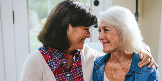 Two aging adult women smiling. Understanding Alzheimer's and Dementia.