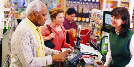 An older adult man purchasing groceries with SNAP Benefits.   (High resolution image available on the link below)