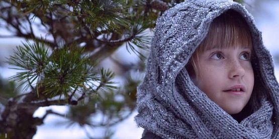 child in knit hood outdoors in the winter before an evergreen