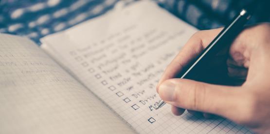 a hand writes down a list
