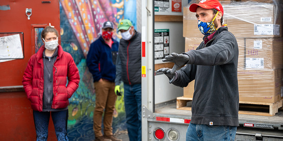 Graham Savino, right, directs volunteers before unloading a truck at of sanitary supplies from NY Ag & Markets