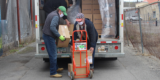 Paul Gier  and Peter Hoyt (right) from Tompkins County Farm Bureau unload materials