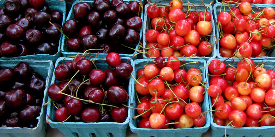 red and yellow cherries, and strawberries at a NYC farmers' market