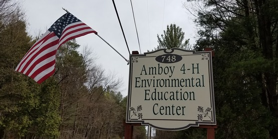 Sign at Amboy 4-H Environmental Education Center with American Flag