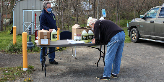 Enfield Code Officer Alan Teeter (left) watches as an ag producer completes paperwork to pick up masks and sanitizer distributed by the NY Dept. of Ag & Markets in response to Covid-19