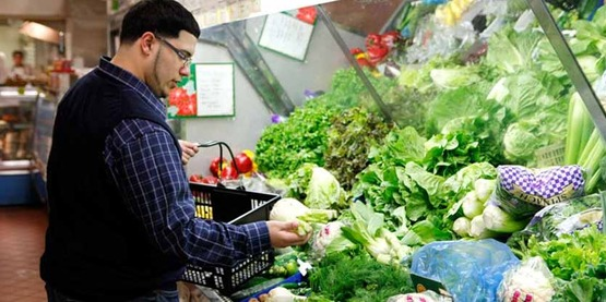 young man chooses produce in a supermarket; shopping