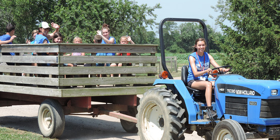 children enjoying a tractor pulled wagon ride at the Suffolk County Farm Camp