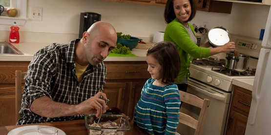 Father and daughter use a food thermometer while a woman cooks in the background