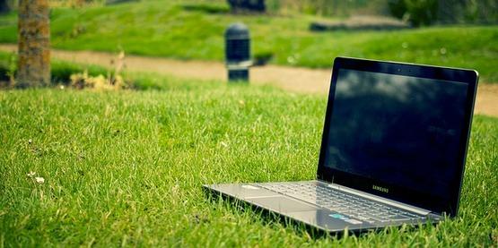 Laptop computer on grass.