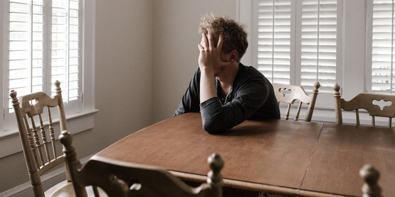 stressed man sitting at dining room table