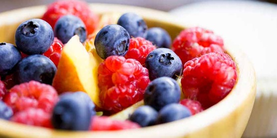 bowl full of healthy fruits: including blueberries and raspberries