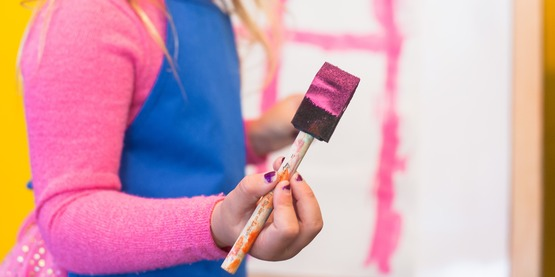 A child holding a sponge brush with pink paint on it.