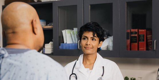 A patient's back out of focus, a doctor in front of him smiling.