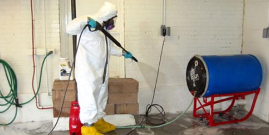 """Using a pressure washer to clean contaminated surfaces; photo from FEMA publication """"Initial Restoration for Flooded Buildings""""."""