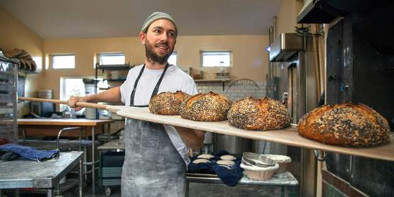 baker uses a peel to put loaves of bread into the oven at Wide Awake Bakery