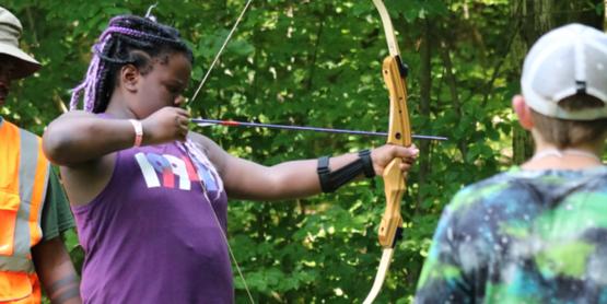 Girl shooting bow and arrow at summer camp