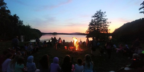Youth around a camp fire at 4-H Camp Wabasso