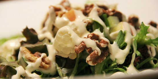 salad topped with nuts and creamy dressing
