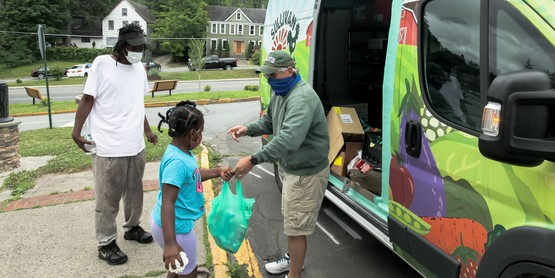 Martin Colavito hands food to a family, from the Sullivan Fresh Community Cupboard