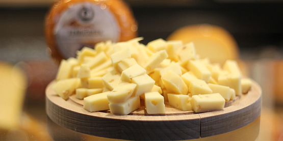 cubes of cheese on a cheese board, blurry round of cheese in background