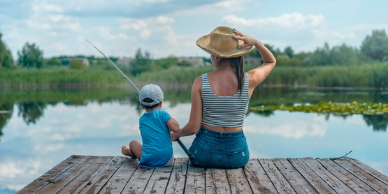 a woman and her son sit at the end of a dock fishing