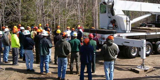 People gather around to learn about crane removal operations from Mark Chisholm, Aspen Tree Care Company.