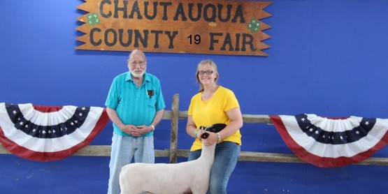 The 4-H Meat Animal Sale will take place Saturday, July 24th at 12:00pm. Pictured is LynnDee Nagel with her market lamb purchased by Stub Porter. Photo courtesy Little Creek Photography.