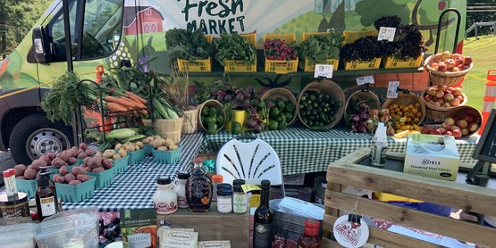 Sullivan Fresh Farmers Market set up with assorted fruits, vegetables, and local products such as coffee, honey, soap, sauces, popcorn.