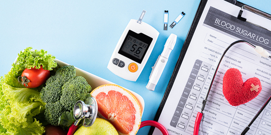 Diabetes glucose meter and blood sugar log next to fruit and vegetables.